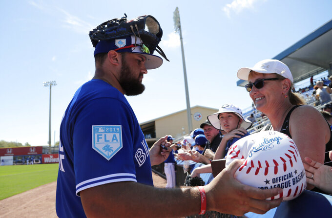 """FILE - Toronto Blue Jays' Rowdy Tellez signs autographs for fans before a spring training baseball game against the Philadelphia Phillies in Dunedin, Fla., in this Thursday, Feb. 28, 2019, file photo. The Toronto Blue Jays will play their first two homestands of the season at their spring training facility in Dunedin, Florida, because of Canadian government restrictions during the pandemic. The team said Thursday, Feb. 18, 2021, it has been planning different scenarios for home games and had hoped to see improvements in public health.  The Blue Jays cited the """"ongoing Canada-U.S. border closure"""" in making the """"difficult decision."""" (AP Photo/Lynne Sladky, File)"""