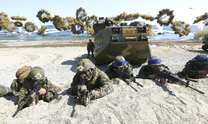 "FILE - In this March 12, 2016, file photo, Marines of the U.S., left, and South Korea wearing blue headbands on their helmets, take positions after landing on a beach during the joint military combined amphibious exercise, called Ssangyong, part of the Key Resolve and Foal Eagle military exercises, in Pohang, South Korea. U.S. President Donald Trump promised to end ""war games"" with South Korea, calling them provocative, after meeting North Korean leader Kim Jong Un on June 12, 2018. His announcement appeared to catch both South Korea and the Pentagon by surprise. (Kim Jun-bum/Yonhap via AP, File)"