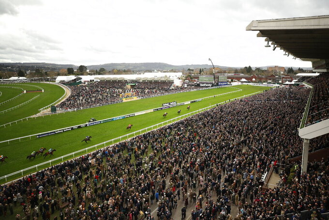 FILE - In this Wednesday March 11, 2020 file photo, a general view from the Grand Stand as Envoi Allen ridden by Davy Russell wins the Ballymore Novices' Hurdle day two of the Cheltenham Horse Racing Festival at Cheltenham Racecourse, England. Cheltenham Festival organisers have defended their decision to go ahead with the meeting last month after fears were raised that the mass gathering of people for the annual horse racing event helped spread coronavirus more widely around Britain. (Tim Goode/PA via AP, File)