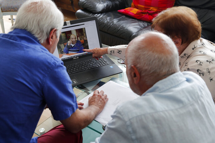 In this photo taken Friday June 5, 2020, Monette Hayoun, Dr Robert Haiun, and Gilbert Haiun, from right, look at photos of their brother Meyer Haiun on a computer during an interview in Ivry sur Seine, south of Paris. Families whose elders died behind the closed doors of homes in lockdown are filing wrongful death lawsuits, triggering police investigations. One suit focuses on the death of Meyer Haiun, a severely disabled 85-year-old in a Paris home managed by a Jewish charitable foundation headed Eric de Rothschild, scion of Europe's most famous banking dynasty. (AP Photo/Francois Mori)