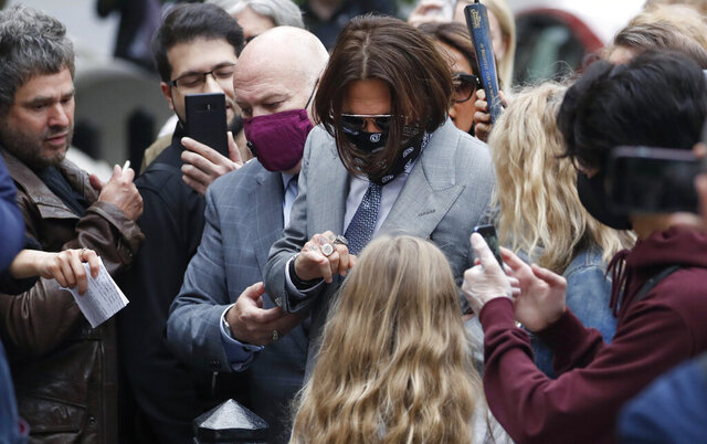 """Actor Johnny Depp, centre, is surrounded by fans as he arrives at the High Court in London, Thursday, July 16, 2020. Depp is suing News Group Newspapers, publisher of The Sun, and the paper's executive editor, Dan Wootton, over an April 2018 article that called him a """"wife-beater."""" The Sun's defense relies on a total of 14 allegations by his ex-wife Amber Heard of Depp's violence. He strongly denies all of them. (AP Photo/Alastair Grant)"""