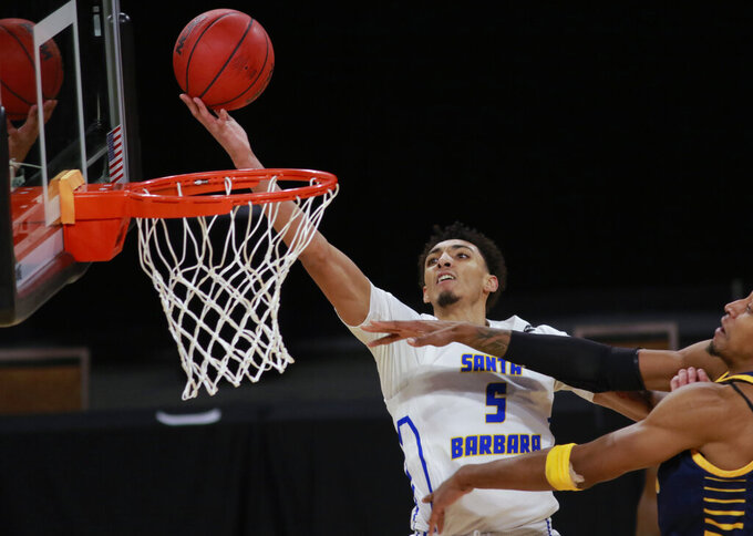 UC Santa Barbara's Miles Norris (5) goes for a shot past UC Irvine's Austin Johnson during the second half of an NCAA college basketball game for the championship of the Big West Conference men's tournament Saturday, March 13, 2021, in Las Vegas. (AP Photo/Ronda Churchill)