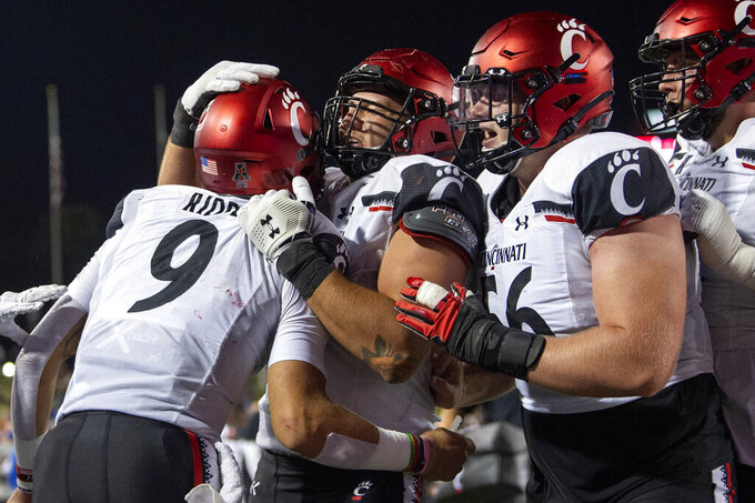Cincinnati quarterback Desmond Ridder (9) is congratulated by offensive linemen Vincent McConnell, center, and Jake Renfro (56) after a touchdown run against SMU during the second half of an NCAA college football game Saturday, Oct. 24, 2020, in Dallas. (AP Photo/Jeffrey McWhorter)