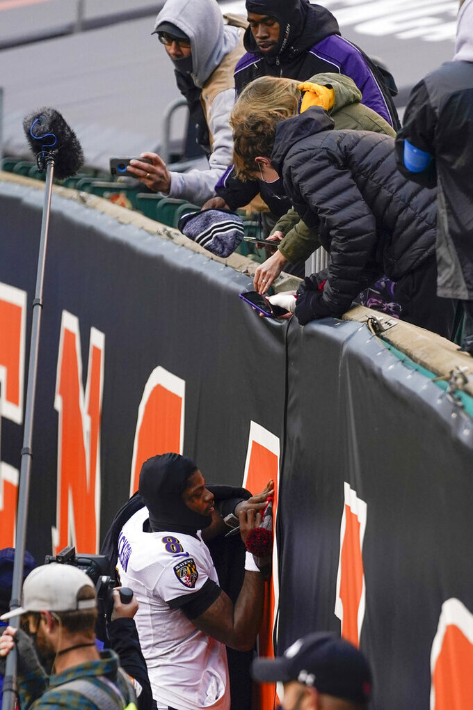 Baltimore Ravens quarterback Lamar Jackson (8) gives an autograph to a fan after the NFL football game against the Cincinnati Bengals, Sunday, Jan. 3, 2021, in Cincinnati. (AP Photo/Bryan Woolston)