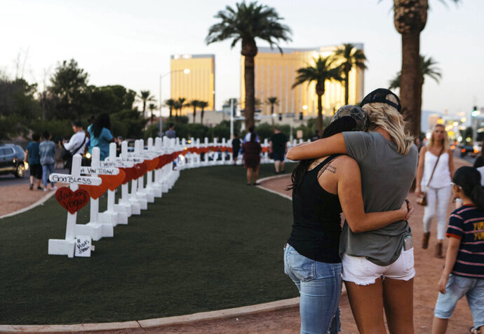 FILE - In this Oct. 5, 2017, file photo, a memorial displaying 58 crosses by Greg Zanis stands at the Welcome To Las Vegas Sign in Las Vegas. Each cross has the name of a victim killed during the mass shooting at the Route 91 Harvest country music festival. Two prominent gun safety organizations say they'll host a forum for Democratic presidential candidates in Las Vegas on Oct. 2, 2019, the day after the second anniversary of the deadliest mass shooting in modern U.S. history. March For Our Lives and the Giffords group told The Associated Press that the forum is the first of its kind for presidential hopefuls. (Mikayla Whitmore/Las Vegas Sun via AP, File)