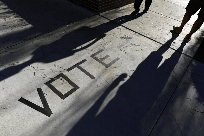 FILE - In this Nov. 6, 2018 file photo, voters head to the polls at the Enterprise Library in Las Vegas. Nevada's Democratic Party has announced new paper-based balloting for its early vote starting Saturday as it scrambles to reconfigure plans and avoid tech problems and reporting delays that mired Iowa's first-in-the-nation caucuses. The party dumped its original plan to have people cast early caucus votes with an app downloaded on iPads. (AP Photo/Joe Buglewicz)
