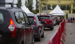 People wait in their cars in a line to be tested at the mobile COVID-19 testing site in Antwerp, Belgium, Tuesday, Oct. 20, 2020. Bars and restaurants across Belgium have been shut down for a month and a night-time curfew entered into force Monday, as health authorities warned of a possible sanitary