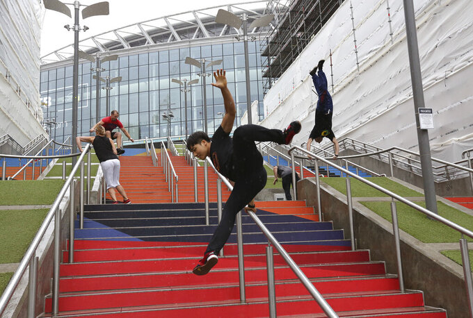 "FILE - In this Aug. 16, 2018, file photo, participants of the Parkour Generations work on their practice runs outside of Wembley Stadium ahead of the 13th Rendezvous International Parkour Gathering in London. Global organizers of parkour are urging the IOC not to add the street-running sport to the 2024 Paris Olympics at a meeting next week. The Parkour Earth group has for years opposed what it calls a ""hostile takeover"" of the sport by the Olympic-recognized International Gymnastics Federation. Parkour Earth said Tuesday, Dec. 1, 2020 in an open letter to the International Olympic Committee that the world gymnastic body's ""encroachment and misappropriation of our sport continues."" (AP Photo/Nishat Ahmed, File)"