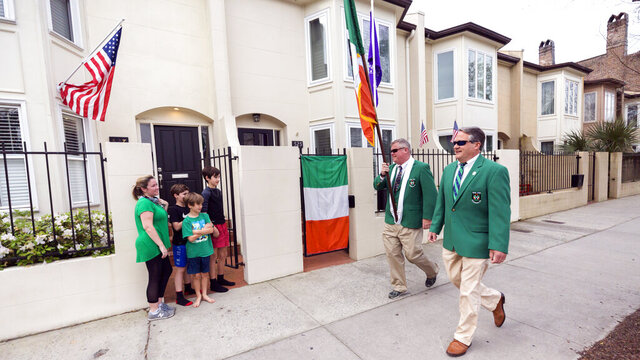 Sinn Fein Society members Bill Bradley, center, and John Lowenthal, right, walk the St. Patrick's Day parade route in downtown Savannah, Ga, Tuesday, March, 17, 2020. Last week Savannah's mayor announced the city's 196-year-old St. Patrick's Day parade was called off due to coronavirus concerns. (AP Photo/Stephen B. Morton)