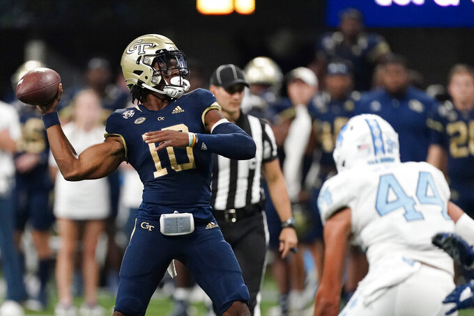 Georgia Tech quarterback Jeff Sims (10) throws a touchdown pass as North Carolina linebacker Jeremiah Gemmel (44) closes in during the second half of an NCAA college football game Saturday, Sept. 25, 2021, in Atlanta. (AP Photo/John Bazemore)