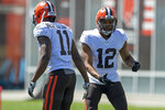 Cleveland Browns receiver Donovan Peoples-Jones, left, is congratulated by receiver KhaDarel Hodge (12) after scoring a touchdown during an NFL football practice in Berea, Ohio, Wednesday, Aug. 4, 2021. (AP Photo/David Dermer)