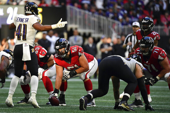 FILE - In this Dec. 2, 2018, file photo, Atlanta Falcons center Alex Mack (51) prepares to work against the Baltimore Ravens during the second half of an NFL football game in Atlanta. Some might argue the center is the most indispensable player on the roster, the player who mans the only position guaranteed to touch the ball on every play. He calls the shots for the line and gets the action going. (AP Photo/Danny Karnik, File)
