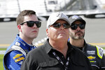 FILE  - In this Sunday, Feb. 11, 2018, file photo, car owner Rick Hendrick, front, stands on pit row with drivers Alex Bowman, left, and Jimmie Johnson before qualifying for the NASCAR Daytona 500 auto race at Daytona International Speedway, in Daytona Beach, Fla. The most coveted seat in NASCAR went to Alex Bowman in a Hendrick Motorsports lineup shuffle to replace seven-time champion Jimmie Johnson in the iconic No. 48 Chevrolet. Bowman and crew chief Greg Ives will move from the No. 88 into Johnson's ride at the end of the season. The swap announced Tuesday, Oct. 6, 2020, makes Bowman just the second driver of the team created in 2001 specifically for Johnson. (AP Photo/Terry Renna, File)