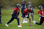 Houston Texans' quarterback Deshaun Watson, 4, stretches next to quarterback AJ McCarron, 2, and quarterback Alex McGough, 3, during an NFL practice session at the London Irish rugby team training ground in the Sunbury-on-Thames suburb of south west London, Friday, Nov. 1, 2019. The Houston Texans are preparing for an NFL regular season game against the Jacksonville Jaguars in London on Sunday. (AP Photo/Matt Dunham)
