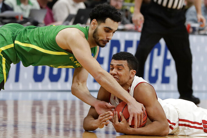 Wisconsin guard D'Mitrik Trice, bottom, holds onto the ball under Oregon guard Ehab Amin during the first half of a first-round game in the NCAA men's college basketball tournament, Friday, March 22, 2019, in San Jose, Calif. (AP Photo/Chris Carlson)