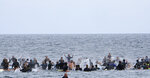 A local group of surfers splash the sea during a traditional paddle out ceremony in Hermosa Beach in support of Black Lives Matter over the death of George Floyd, in Los Angeles on Friday June 5, 2020. Floyd, a black man, died after he was restrained by Minneapolis police on May 25. (AP Photo/Richard Vogel)