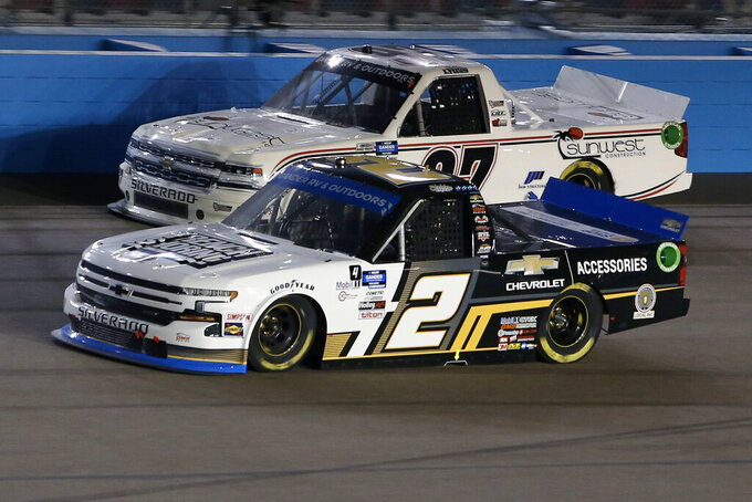 Sheldon Creed (2) races Robby Lyons (97) through Turn 4 during a NASCAR Truck Series auto race at Phoenix Raceway, Friday, Nov. 6, 2020, in Avondale, Ariz. (AP Photo/Ralph Freso)