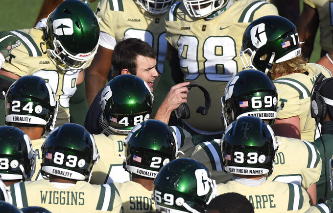 Charlotte head coach Will Healy, center, gives instructions to his team prior to the start of the fourth quarter against Western Kentucky in an NCAA college football game on Sunday, Dec. 6, 2020. (Jeff Siner/The Charlotte Observer via AP)
