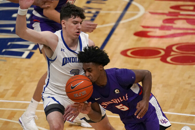 Evansville's Shamar Givance (5) loses control of the ball on his way to the basket as Indiana State's Jake LaRavia defends during the first half of an NCAA college basketball game in the quarterfinal round of the Missouri Valley Conference men's tournament Friday, March 5, 2021, in St. Louis. (AP Photo/Jeff Roberson)