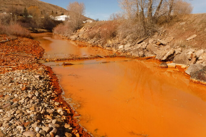 FILE - This March 7, 2016 photo provided by the Montana Department of Environmental Quality shows a polluted Belt Creek in Montana. The state plans to build a plant to treat acid mine drainage from an old coal mine that is polluting Belt Creek, sometimes causing it to turn a rusty color and harming the trout fishery. (Tom Henderson/Montana Department of Environmental Quality via AP)