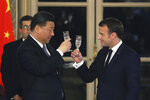 French President Emmanuel Macron, right, and Chinese President Xi Jinping share a toast during a state dinner at the Elysee Palace in Paris, France, Monday, March 25, 2019. Chinese President Xi Jinping is on a 3-day state visit in France where he is expected to sign a series of bilateral and economic deals on energy, the food industry, transport and other sectors. (Ludovic Marin/Pool Photo via AP)