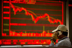 A Chinese investor talks on his cellphone as he monitors stock prices at a brokerage house in Beijing, China, Thursday, Aug. 9, 2018. (AP Photo/Mark Schiefelbein)