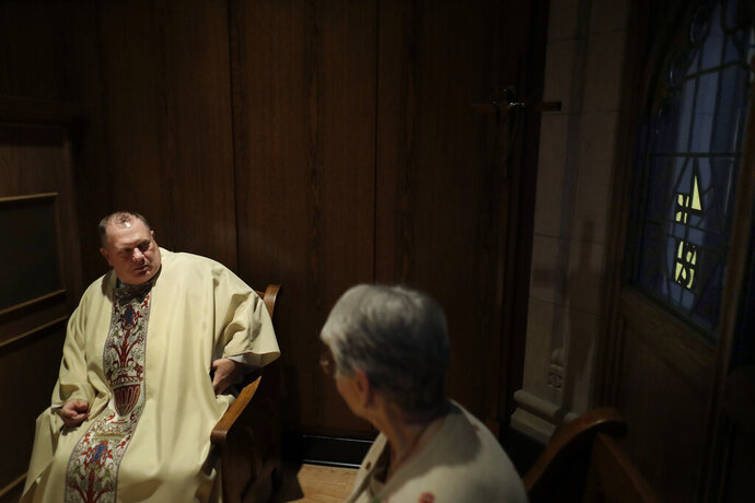 In this Thursday, Oct. 31, 2019 photo, Rev. Mark Stelzer, a professor and chaplain at College of Our Lady of the Elms, speaks with sacristan Marlene Czepiel, right, in the sacristy before offering Mass in the school's chapel, in Chicopee, Mass. Stelzer is also administrator of St. Jerome's Parish, in Holyoke, Mass., where he lives alone in a rectory while serving as spiritual leader to the 500 families in the Catholic parish. (AP Photo/Steven Senne)