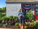 In this Friday, June 7, 2019, photo provided by Alicia Jessop, Jessop poses for a photo with a lobster roll at Fox's Lobster House in York, Maine. Jessop wanted to snap the perfect picture Friday of her lobster roll from Fox's Lobster House in York, Maine, before she took a bite. She says she was focused on framing the sandwich with the picturesque Nubble Lighthouse in the background when she felt something rustle her hand. She quickly realized a seagull had knocked it out of her hand and was already eating it. (Alicia Jessop/@rulingsports via AP)