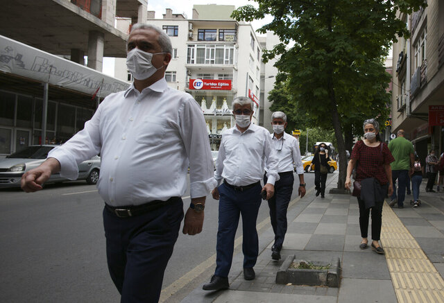 A woman watches the men wearing face masks for protection against the coronavirus and respecting social distance, in popular Tunali Hilmi Street, in Ankara, Turkey, Wednesday, May 27, 2020. Turkish children under 14 were allowed to go out between 12:00-15:00 local time for the third time. (AP Photo/Burhan Ozbilici)