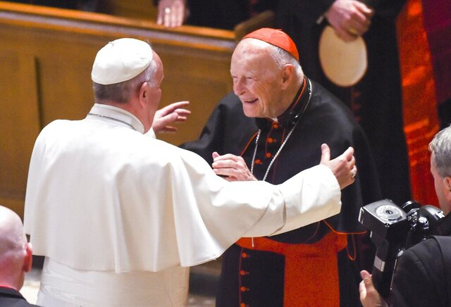 FILE - In this Sept. 23, 2015 file photo, Pope Francis reaches out to hug Cardinal Archbishop emeritus Theodore McCarrick after the Midday Prayer of the Divine with more than 300 U.S. bishops, at the Cathedral of St. Matthew the Apostle in Washington. On Tuesday, Nov. 10, 2020, the Vatican is taking the extraordinary step of publishing its two-year investigation into the disgraced ex-Cardinal McCarrick, who was defrocked in 2019 after the Vatican determined that years of rumors that he was a sexual predator were true. (Jonathan Newton/The Washington Post via AP, File)