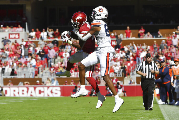 Arkansas defensive back Montaric Brown (21) intercepts a pass intended for Auburn receiver Ze'Vian Capers (80) during the first half of an NCAA college football game Saturday, Oct. 16, 2021, in Fayetteville, Ark. (AP Photo/Michael Woods)