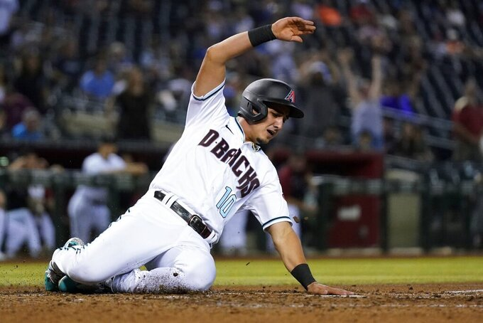 Arizona Diamondbacks' Josh Rojas scores against the Pittsburgh Pirates during the fourth inning of a baseball game Tuesday, July 20, 2021, in Phoenix. (AP Photo/Ross D. Franklin)