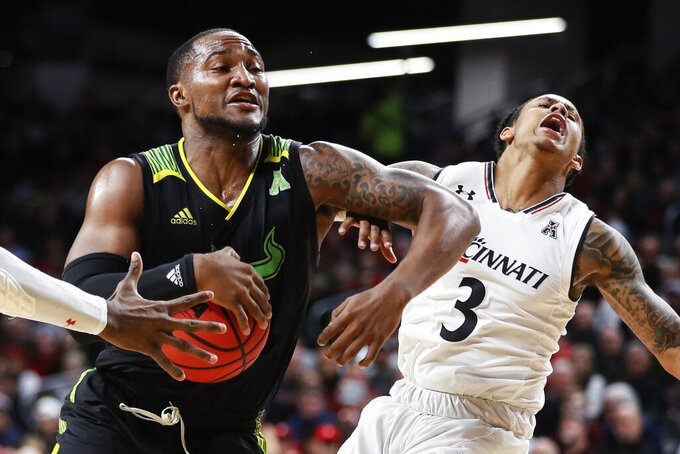 South Florida's LaQuincy Rideau, left, drives against Cincinnati's Justin Jenifer (3) in the second half of an NCAA college basketball game, Tuesday, Jan. 15, 2019, in Cincinnati. (AP Photo/John Minchillo)