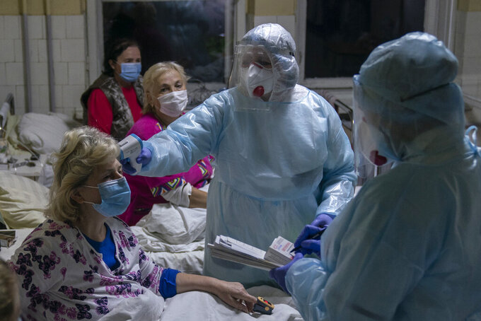 A nurse checks the temperature of a patient with coronavirus in Stebnyk, western Ukraine, on Tuesday, Sept. 29, 2020. As coronavirus cases increase, every bed in the hospital in this city in western Ukraine is in use and its chief doctor is watching the surge with alarm and anguish. (AP Photo/Evgeniy Maloletka)