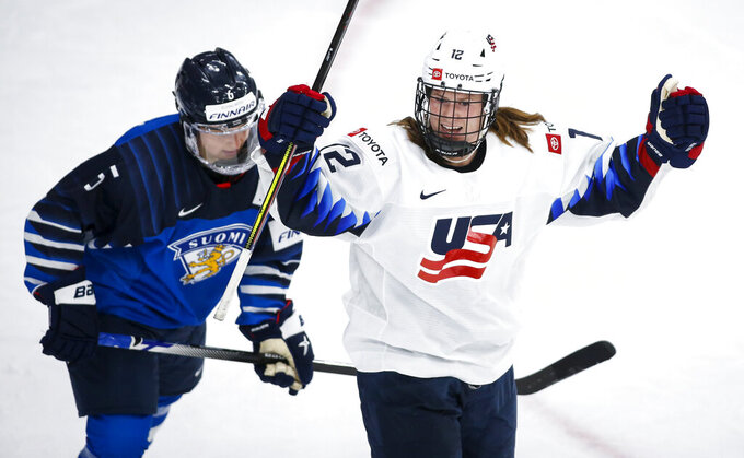 Kelly Pannek, right, of the United States, celebrates her goal as Finland's Jenni Hiirikoski skates past during second period IIHF women's world championship hockey action in Calgary, Alberta, Sunday, Aug. 22, 2021. (Jeff McIntosh/The Canadian Press via AP)