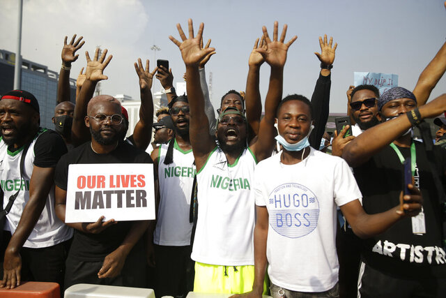 People hold banners as they demonstrate on the street to protest against police brutality in Lagos, Nigeria, Tuesday Oct. 13, 2020. Crowds protesting against police brutality in Nigeria have taken to the streets for a sixth day across Africa's most populous nation. Fresh protests took place in Nigeria's largest city, Lagos, and in the southeastern cities of Port Harcourt and Uyo on Tuesday. (AP Photo/Sunday Alamba)