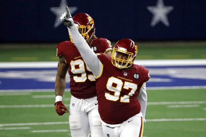 Washington Football Team's Tim Settle (97) celebrates in front of Chase Young (99) after sacking Dallas Cowboys quarterback Andy Dalton in the second half of an NFL football game in Arlington, Texas, Thursday, Nov. 26, 2020. (AP Photo/Roger Steinman)
