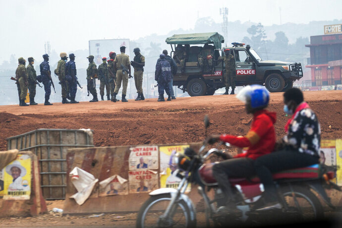 Security forces gather in Kampala, Uganda, Thursday, Jan. 14, 2021. Ugandans are voting in a presidential election tainted by widespread violence that some fear could escalate as security forces try to stop supporters of leading opposition challenger BobiWine from monitoring polling stations.(AP Photo/Jerome Delay)