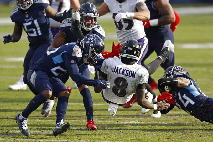 Baltimore Ravens quarterback Lamar Jackson (8) is upended as he scrambles against the Tennessee Titans in the second half of an NFL wild-card playoff football game Sunday, Jan. 10, 2021, in Nashville, Tenn. (AP Photo/Wade Payne)