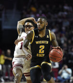 Wichita State's Jamarius Burton (2) brings the ball up court past Temple's Nate Pierre-Louis (15) during the first half of an NCAA college basketball game Wednesday, Jan. 15, 2020, in Philadelphia. (AP Photo/Michael Perez)