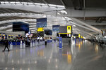 Terminal 5 at Heathrow Airport in London, which handles British Airways flights, stands virtually empty of passengers as staff are seen during a British Airways pilots' strike, Monday, Sept. 9, 2019. British Airways says it has had to cancel almost all flights as a result of a pilots' 48-hour strike over pay. (AP Photo/Matt Dunham)