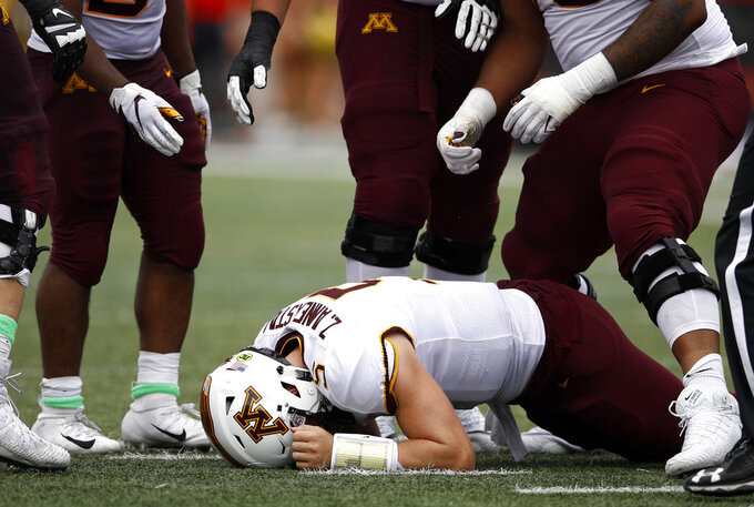 FILE - In this Sept. 22, 2018, file photo, teammates surround Minnesota quarterback Zack Annexstad as he reacts after turning over the ball on downs to Maryland in the second half of an NCAA college football game, in College Park, Md. Iowa's dominant defensive line will be a major challenge for Minnesota freshman quarterback Zack Annexstad, in the latest edition of the Floyd of Rosedale bronze pig trophy game. (AP Photo/Patrick Semansky, File)