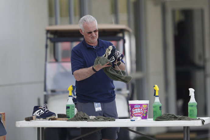 A member of the Boston Red Sox staff cleans shoes as pitchers and catchers report for spring training baseball Tuesday, Feb. 11, 2020, in Fort Myers, Fla. (AP Photo/John Bazemore)