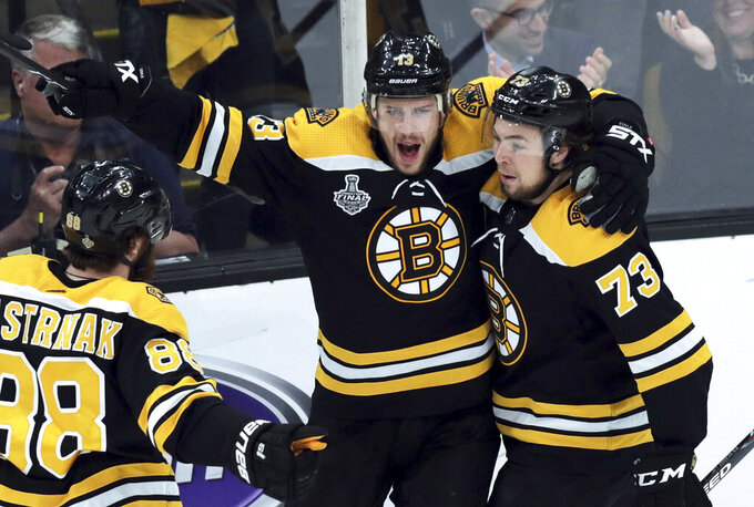 Boston Bruins' Charlie Coyle, center, celebrates his power play goal with David Pastrnak, left, of the Czech Republic, and Charlie McAvoy, right, during the first period in Game 2 of the NHL hockey Stanley Cup Final against the St. Louis Blues, Wednesday, May 29, 2019, in Boston. (AP Photo/Charles Krupa)