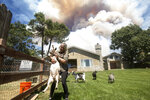 Diane Brickley comes back home to take care her goats after she was evacuated as the Apple Fire burns nearby in Cherry Valley, Calif., Saturday, Aug. 1, 2020. A wildfire northwest of Palm Springs flared up Saturday afternoon, prompting authorities to issue new evacuation orders as firefighters fought the blaze in triple-degree heat. (AP Photo/Ringo H.W. Chiu)