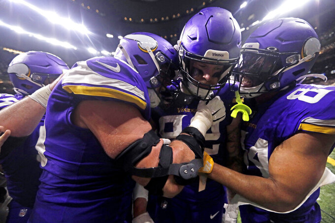Minnesota Vikings tight end Kyle Rudolph, center, is congratulated by teammates after catching the game winning touchdown pass during overtime of an NFL wild-card playoff football game against the Minnesota Vikings, Sunday, Jan. 5, 2020, in New Orleans. The Vikings won 26-20. (AP Photo/Brett Duke)