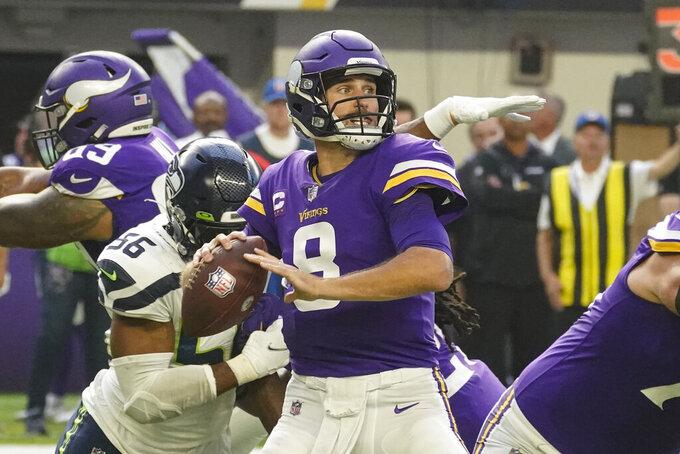Minnesota Vikings quarterback Kirk Cousins (8) throws under pressure from Seattle Seahawks linebacker Jordyn Brooks (56) in the first half of an NFL football game in Minneapolis, Sunday, Sept. 26, 2021. (AP Photo/Jim Mone)