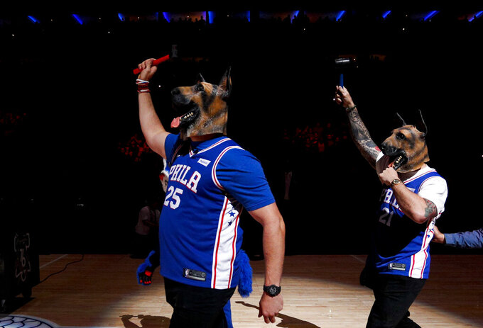 Philadelphia Eagles' Lane Johnson, left, and Chris Long acknowledge the crowd before Game 6 of the second-round NBA basketball playoff series between the Philadelphia 76ers and the Toronto Raptors, Thursday, May 9, 2019, in Philadelphia. (AP Photo/Chris Szagola)