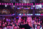 An attendee takes a video shot of the room during the opening of the Web Summit technology conference in Lisbon, Monday, Nov. 4, 2019. (AP Photo/Armando Franca)