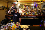 Michael Neff, co-owner of the Cottonmouth Club, adjusts his hat as he stands behind the bar Tuesday, June 23, 2020, in Houston. Neff closed his downtown bar because of concerns within the industry as the number COVID-19 case continues to rise in Houston. (AP Photo/David J. Phillip)